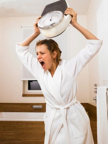 Angry Woman Throwing Scale --- Image by © Morgan David de Lossy/Corbis
